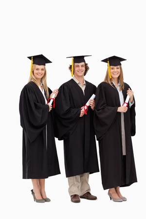 Three smiling students in graduate robe holding a diploma against white background photo