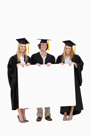 Three students in graduate robe holding a blank sign against white background photo