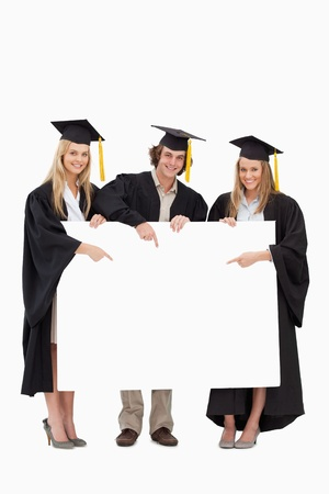 university sign: Three students in graduate robe holding and pointing a blank sign against white background