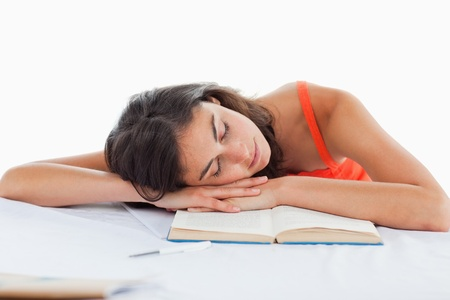 Sleeping student head on her books against white background photo