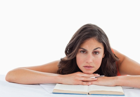 Frowning student head on her books against white background photo