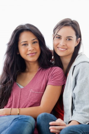 looking towards camera: A half length shot of two women on the couch looking towards the camera while they both smile Stock Photo