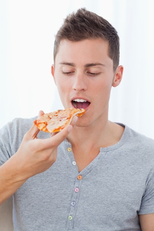 A close up shot of a man as he looks at the slice of pizza he is about to eat  Stock Photo - 16058121