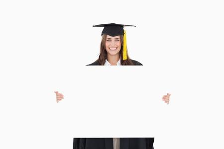 hoja en blanco: Una mujer sonriente mirando a la c�mara mientras sostiene una hoja en blanco delante de ella Foto de archivo