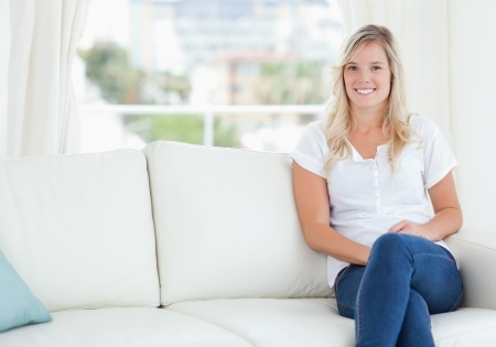crossed legs: A smiling woman sitting on her couch in her house Stock Photo