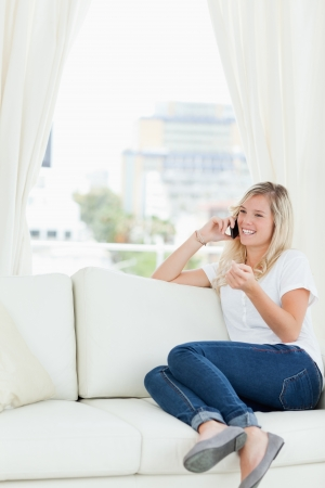 A smiling woman with her hand slightly raised as she sits on her couch making a call Stock Photo - 16051837