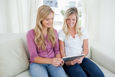 Two smiling sisters look at a tablet together as they sit on the couch Stock Photo - 16065504