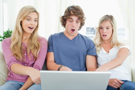 Three shocked siblings as they look at the laptop screen Stock Photo - 16069468