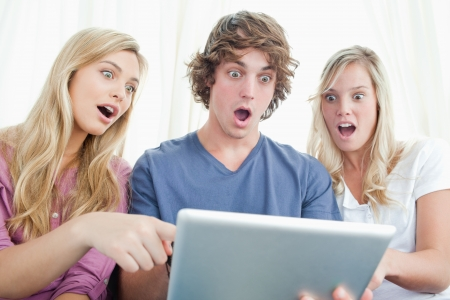 Three friends looking at the screen of the tablet and looking shocked