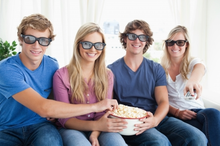 they are watching: Smiling friends watching a funny movie in 3d as they all eat some popcorn  Stock Photo