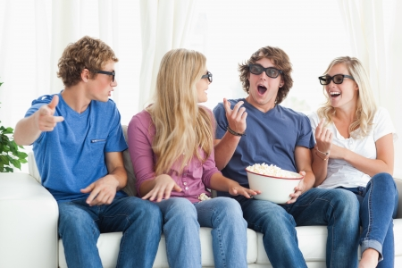 A group of friends laugh and joke around as they wear 3d glasses photo