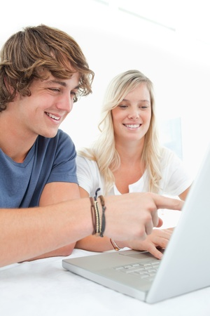 A couple sit at the table as they look at a laptop as the guy points to the laptop screen Stock Photo - 16053414
