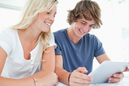 A couple sit and smile as they both use a tablet Stock Photo - 16056976