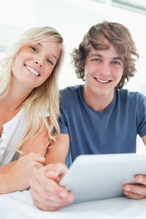 A smiling couple holding a tablet and looking at the camera while they sit together Stock Photo - 16055567