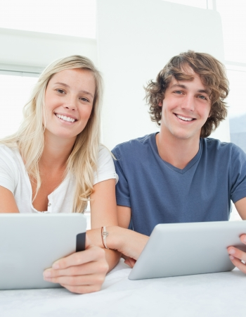 A smiling couple looking at the camera as they both hold tablets  Stock Photo - 16054448