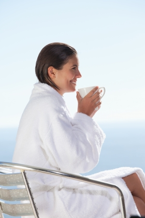 Side view of smiling woman in bathrobe drinking coffee photo