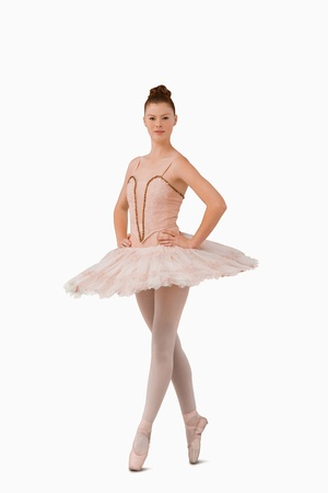 on tiptoes: Ballerina standing on her tiptoes against a white background