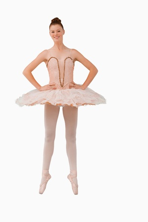 tiptoes: Smiling ballerina standing on her tiptoes against a white background Stock Photo