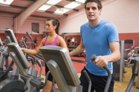 Woman and man training on a step machine in gym photo