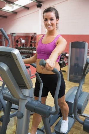 Woman stepping on a step machine in gym photo