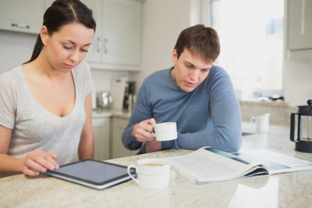 Two people reading from tablet pc and newspaper in kitchen photo