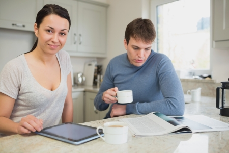 friendliness: Two people sitting in the kitchen reading news and drinking coffee Stock Photo