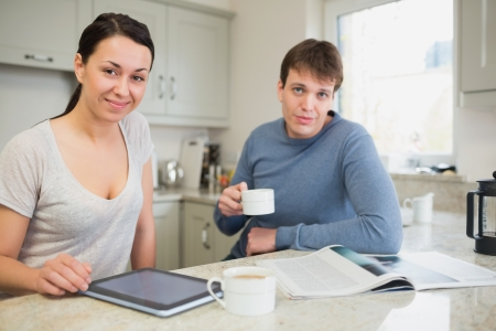 Smiling woman with tablet pc and man with newspaper drinking coffee in kitchen photo
