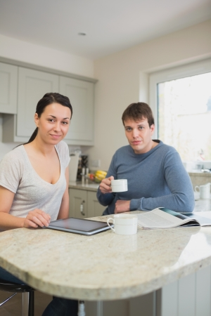 Two people sitting in the kitchen, drinking coffee and relaxing photo