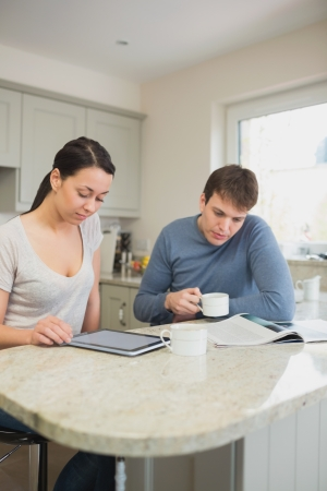 Two people reading from tablet pc and magazine in kitchen photo