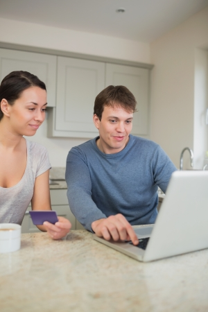 Two people sitting in the kitchen purchasing online on laptop in kitchen photo