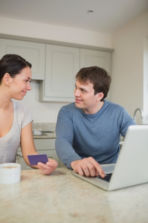Couple using credit card online in kitchen photo