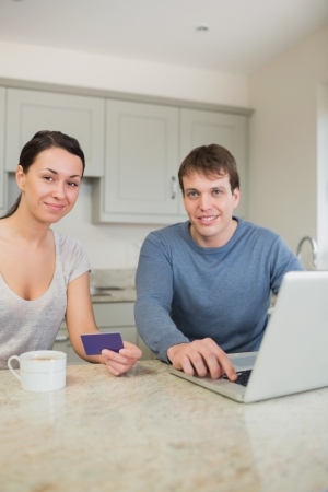 Couple sitting in the kitchen with a laptop and a credit card while drinking coffee photo