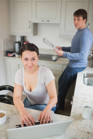 Young woman using laptop with man reading magazine in kitchen  photo