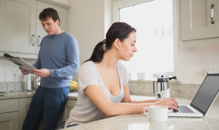 Two people in the kitchen who are using the laptop and reading a magazine photo