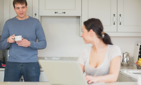 Two people spending time in the kitchen while using the laptop and drinking Stock Photo - 16053415