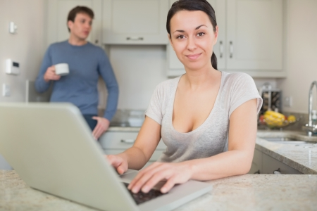 Young woman using laptop with man drinking coffee in kitchen Stock Photo