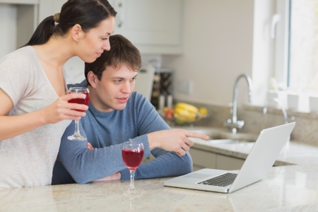 Couple drinking red wine and using laptop in kitchen photo