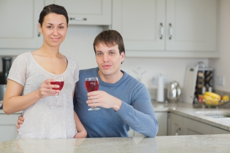 Two people enjoying the togetherness while drinking wine in the kitchen Stock Photo - 16055202