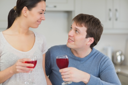 Cute couple drinking red wine and looking fondly at each other in kitchen Stock Photo - 16054670