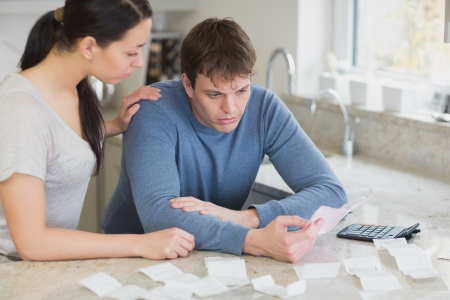 Couple calculating bills in kitchen looking worried  photo