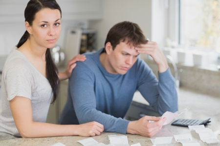 Two people in the kitchen calculating finances with calculator Stock Photo - 16055114