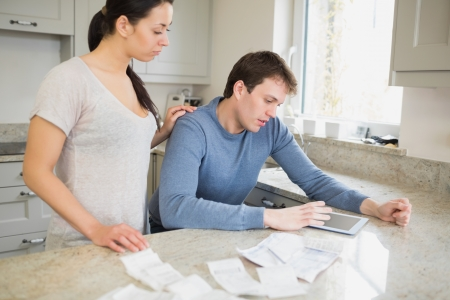 Couple using tablet pc to calculate finances in kitchen Stock Photo - 16055196