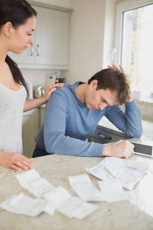 Wife comforting stressed husband over bills in kitchen with tablet pc photo