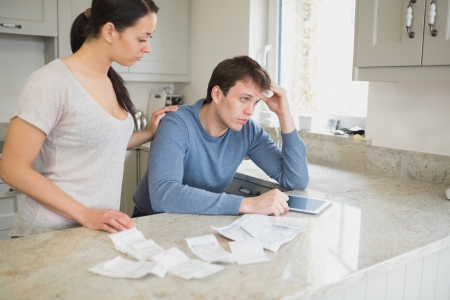Two people calculating finances in the kitchen and using tablet pc photo