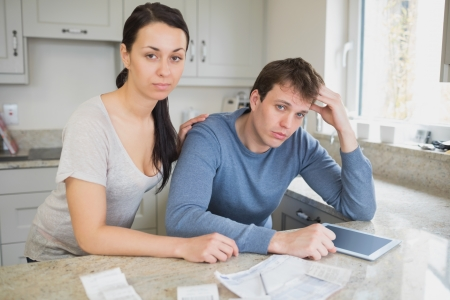 Two people in the kitchen are calculating the finances with an ebook photo