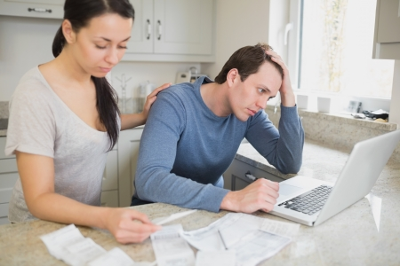 Two people calculating finances and using the laptop photo
