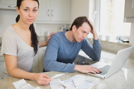 Two people focused on finances while using the laptop in the kitchen photo