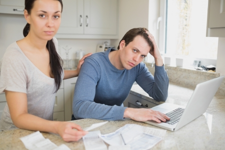 Two people focused on finances while working on the laptop in the kitchen photo
