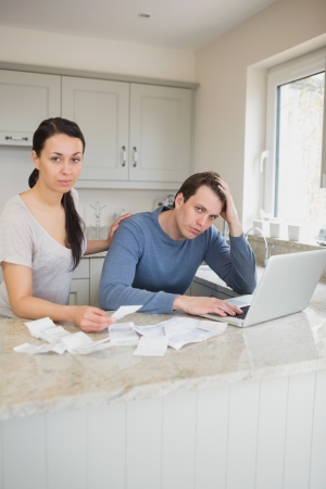 Two people working on finances while using the laptop in the kitchen photo