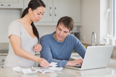 Two people working on finances and using the laptop in the kitchen photo